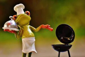 Chef cuisinier grenouille avec plat à la main et barbecue ouvert à droite