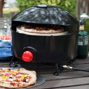 Four à pizza gaz noir posé sur table avec pizza devant