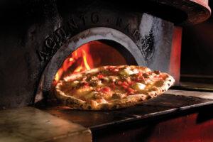 Four à pizza à l'ancienne avec pizza en chauffe devant