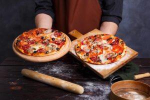 Présentation de 2 pizzas en main par chef pizzaïolo